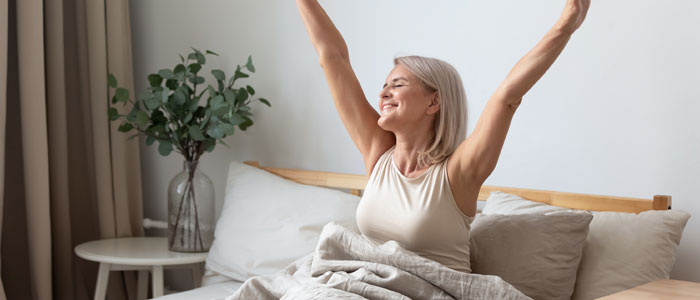 older woman in bed, happy and stretching, the benefits of being outdoors