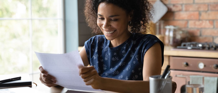 woman sat at a table looking at some documents, smiling.