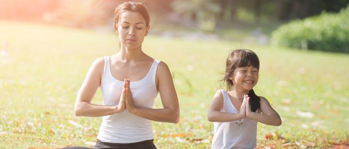 woamn and small girl doing yoga outside