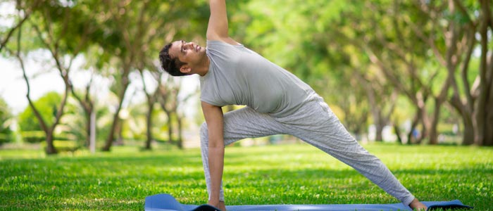 man doing yoga on a mat in the park