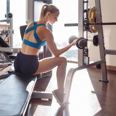 woman sat on a weight bench doing bicep curls with dumbbells