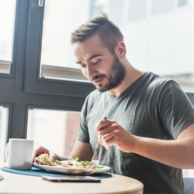man sat at a table eating a healthy meal