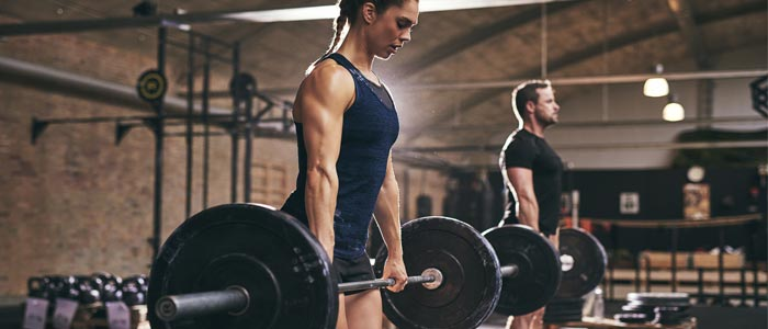 woman and man doing deadlifts with weights and barbells