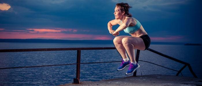 woman outside doing squat jumps