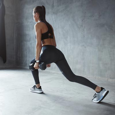 Woman doing walking lunges at home