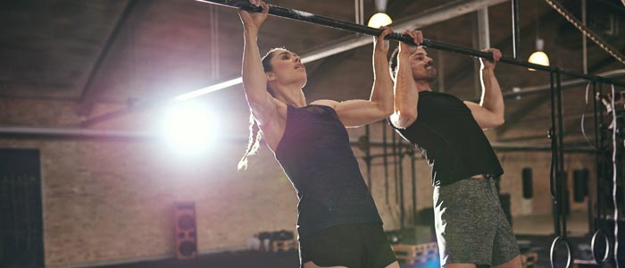 Couple performing pull-ups