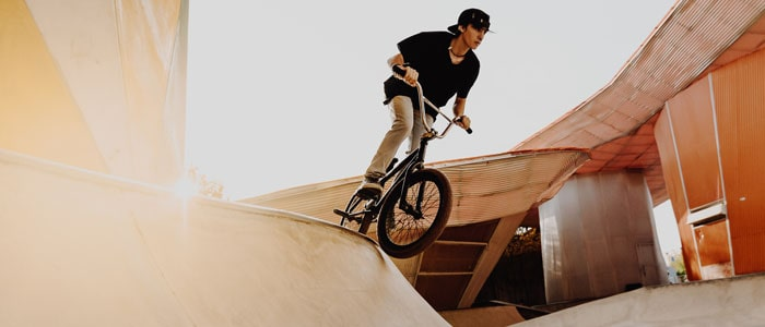 person at a BMX park, perparing to try a trick