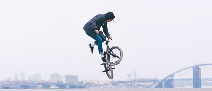 person outside BMX biking, in the air flipping the bike