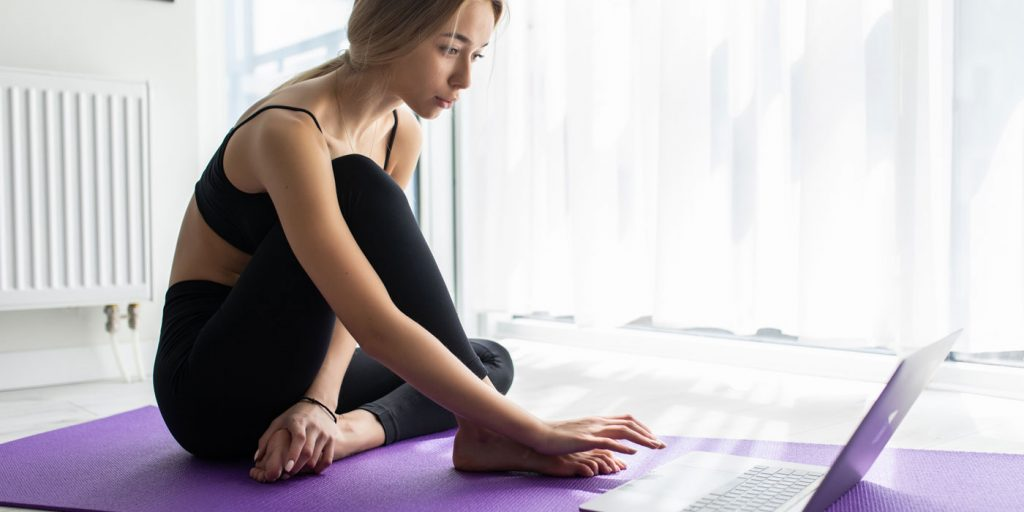 woman sat on a yoga mat planning her workouts