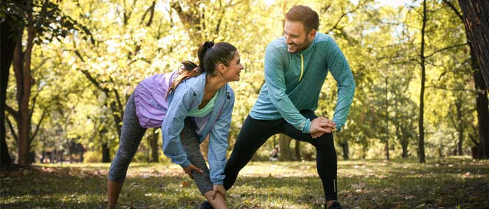 man and woman stretching in the park together
