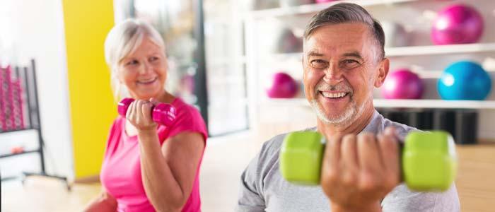elderly couple training with dumbbells