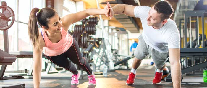 man and woman high fiving whilst doing push ups in the gym