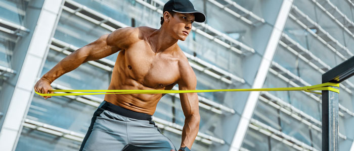 man outside with a resistance band tied to a post, strengthening his arms and upper body.