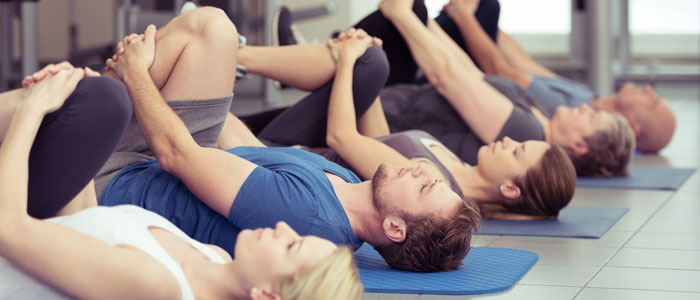 group of people stretching with their leg to their chest