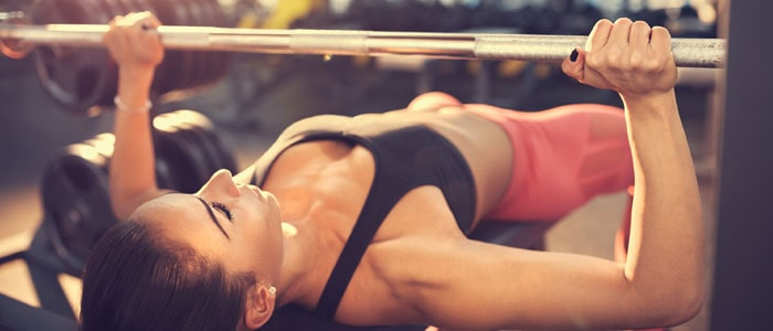 a woman in the gym doing a bench press as a strength training exercise for tennis