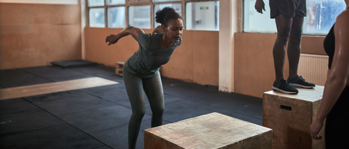 a woman doing box jumps as a strength training exercise for tennis