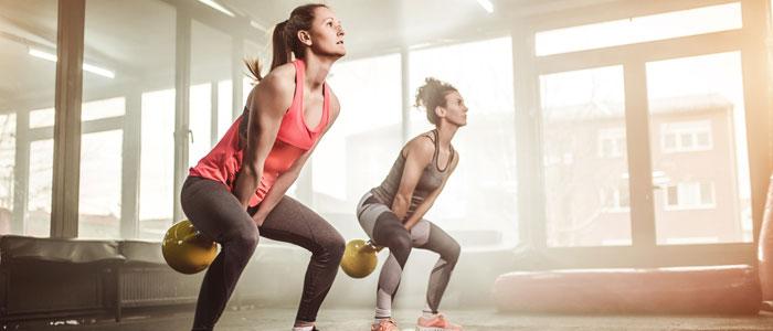 2 women doing kettlebell swings as a strength training exercise for tennis