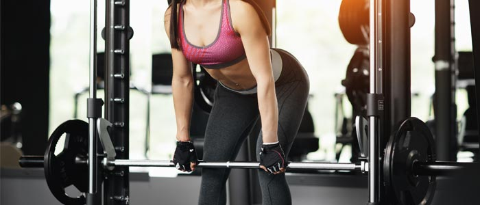 Woman performing rack pulls in a smith machine