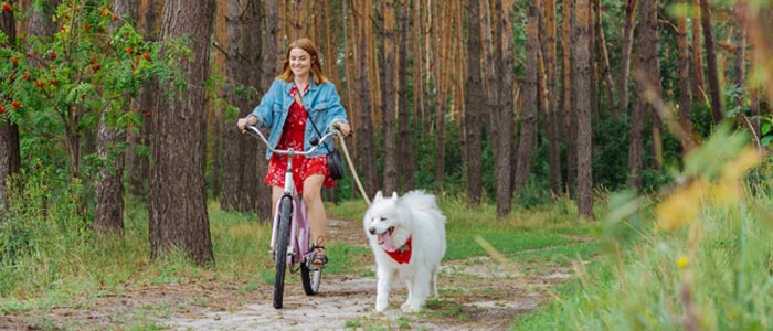 woman cycling in the woods with a dog running beside her