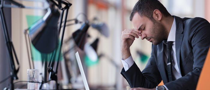 Man sat at a desk, head in hands, looking tired