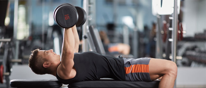 man doing chest exercises with dumbbells