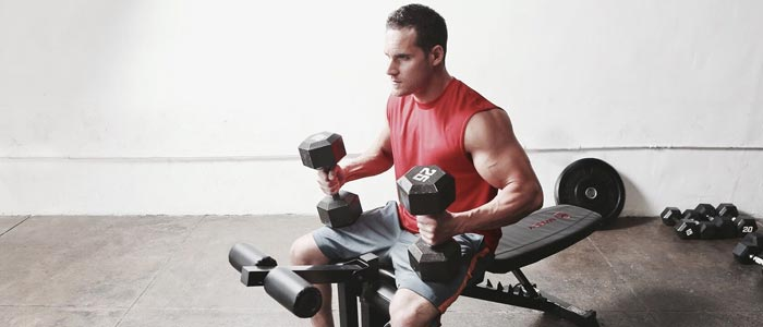 man sat on a weight bench with some dumbbells