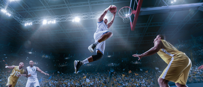 Man in the air about to score a hoop in basketball, other men around the court.