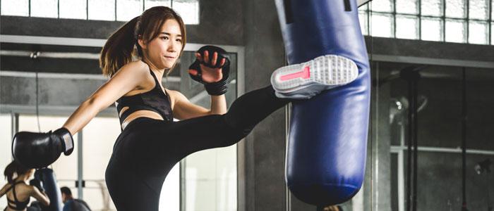 woman kicking a boxing bag