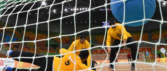 Players defending a goal, whilst the ball hits the net