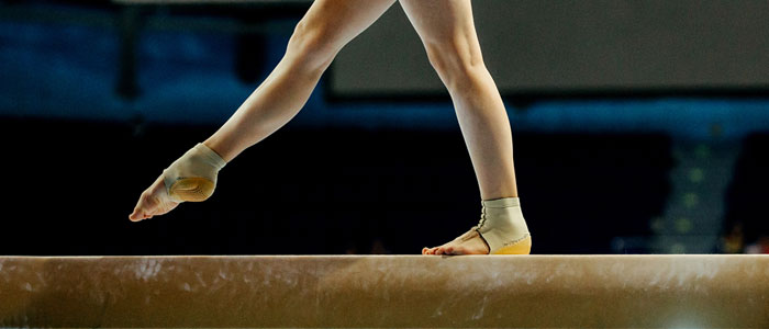 woman balancing on a gymnastics beam