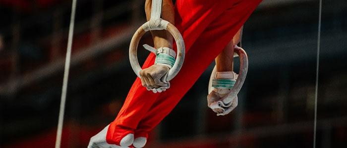 man doing exercises on gymnastics rings