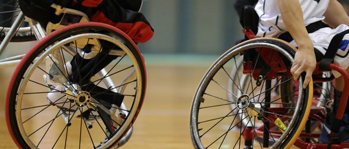 two people in wheelchairs playing basketball