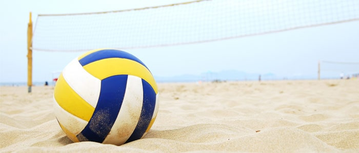 A volleyball on the beach in front of a net