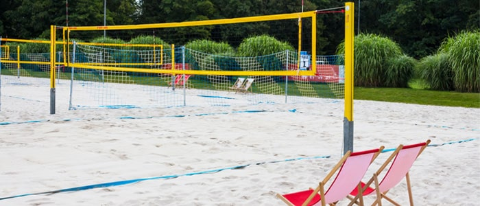 A beach volleyball court with a net and beach chairs nearby