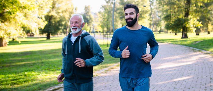 younger and older man running in the park together
