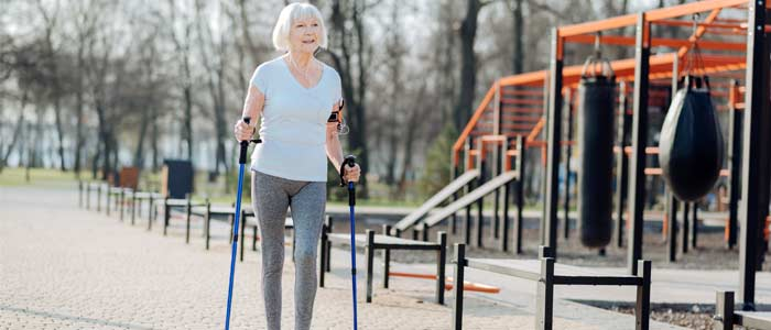 woman out walking with walking sticks for support