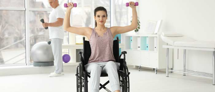woman in a wheelchair lifting dumbbells