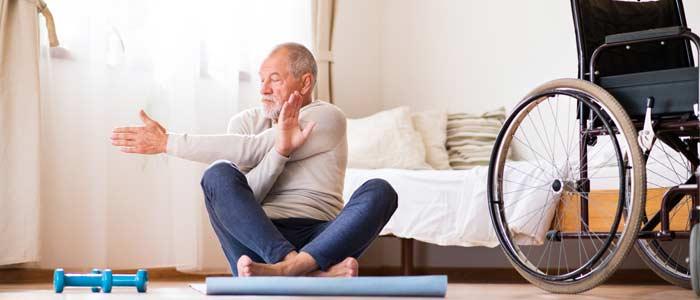 elderly man sat on the floor doing stretches.