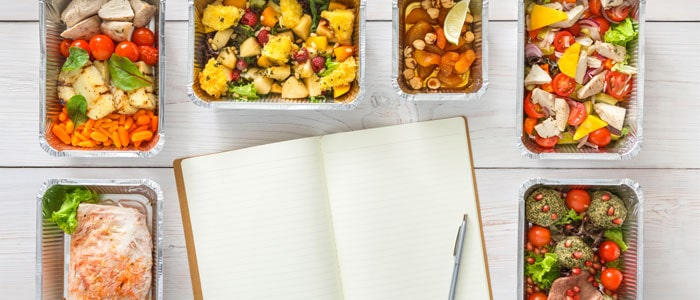 different healthy meals around a notebook to create a meal plan.