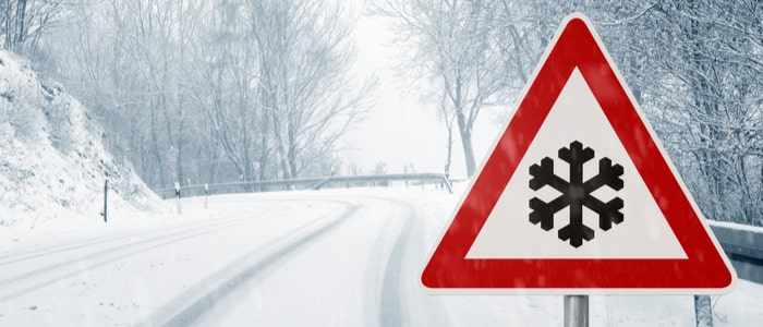 a winding country road in winter with a road sign showing a risk of snow and ice