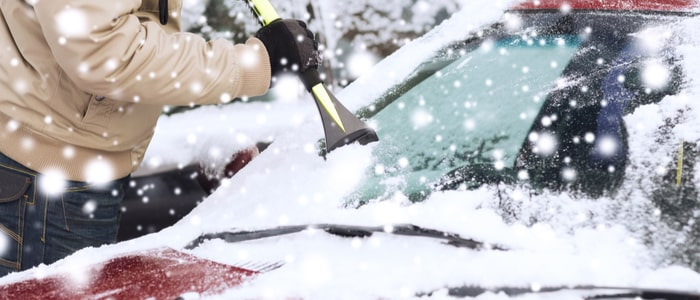 closeup of a man cleaning snow from a car windshield with a brush