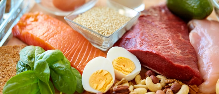 A close up image of some raw fish salmon. and meat. Also includes some eggs, green leaves and various nuts. Items you could add to your diet to help depression.