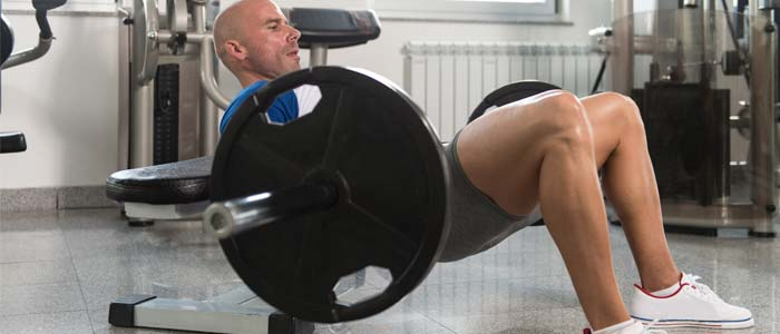 man using a barbell and weight bench to do a glute bridge