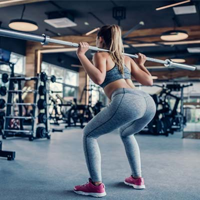 Woman doing squats glute exercise in the gym