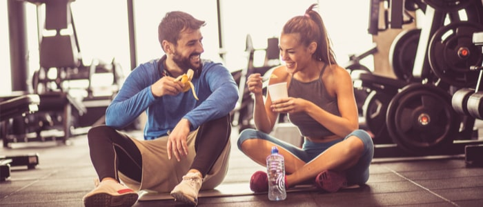 A man and woman eating a healthy snack after working out at the gym.