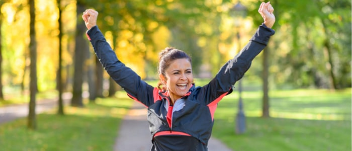 Happy middle aged woman cheering and celebrating as she walks along a rural lane through a leafy green park after working out